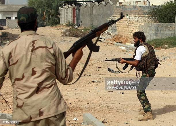 Libyan fighters loyal to the National Transitional Council take cover during fighting against troops loyal to former leader Moamer Kadhafi in the...