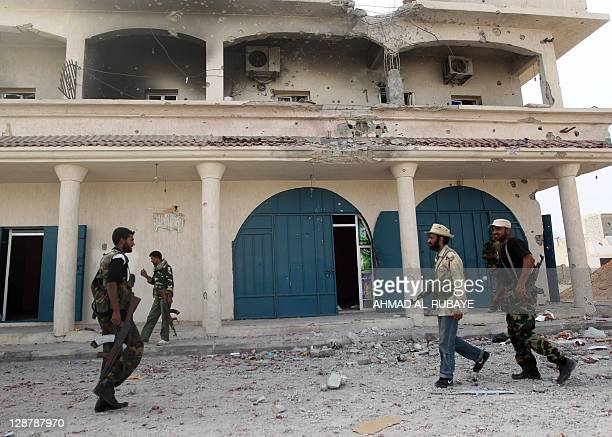Libyan fighters loyal to the National Transitional Council walk past a destroyed building as they battle against troops loyal to former leader Moamer...