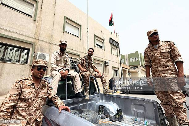 Libyan gunmen surround the Libyan Justice Ministry demanding a ban against those who worked under the former regime of ousted leader Moamer Kadhafi...