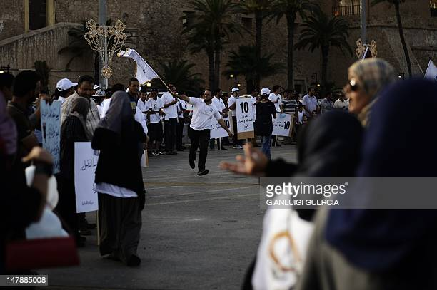 A Libyan Justice and Construction supporter runs with national and party flags during a Libyan National Assembly Campaign rally at Martyrs Square on...