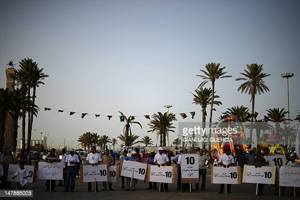 Libyan Justice and Construction supporters hold party signs during a Libyan National Assembly Campaign rally at Martyrs Square on July 5 2012 in...