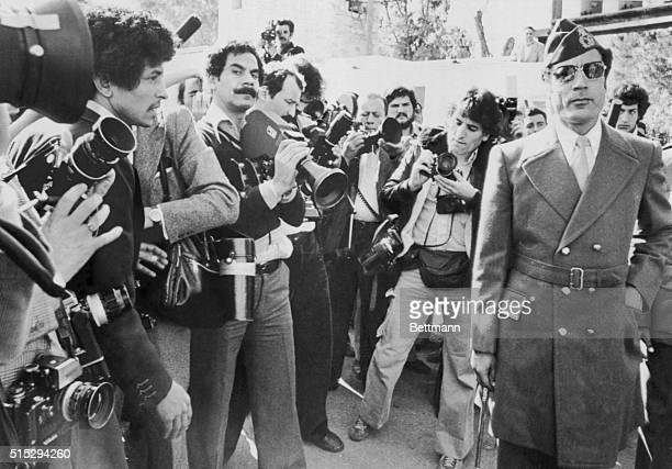 Libyan leader Colonel Muammar alQaddafi bypasses a dozen cameramen and photographers as he arrives at Tripoli military airport to welcome Arab chiefs...