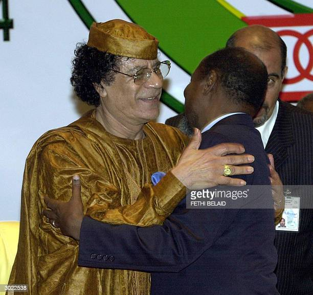 Libyan leader Moamer Kadhafi greets Mozambican President and current chairperson of the African Union Joaquim Chissano at the end of the African...