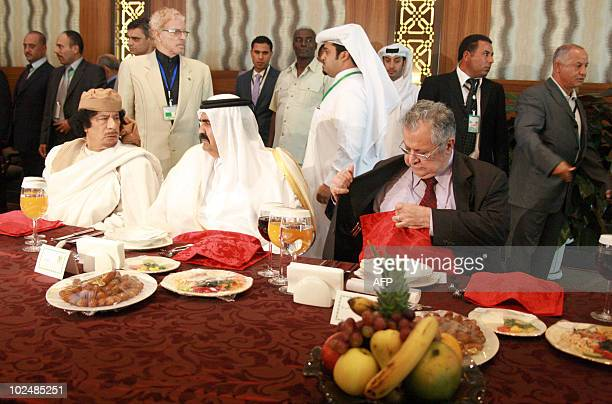 Libyan leader Moamer Kadhafi speaks to the Emir of Qatar Sheikh Hamad bin Khalifa al-Thani as the Iraqi President Jalal Talabani sits by as they...