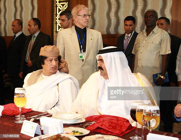 Libyan leader Moamer Kadhafi speaks to the Emir of Qatar Sheikh Hamad bin Khalifa al-Thani as they attend a mini-summit of five Arab states -Libya,...