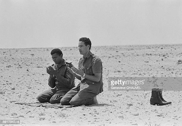 Libyan Leader Muammar alQaddafi joins another Muslim man in prayer in the Syrtes Desert Libya