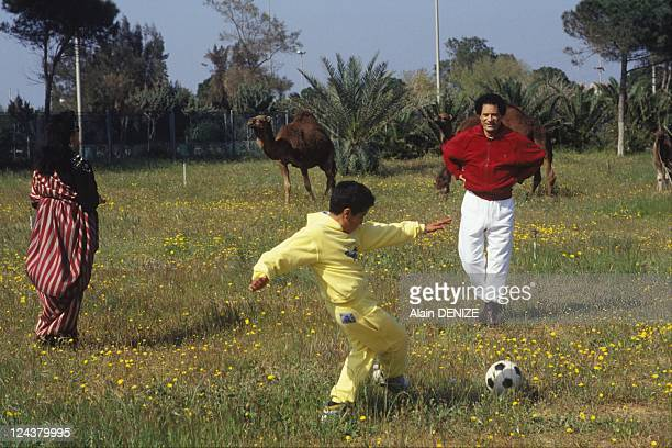 Libyan leader Muammar Gaddafi and his wife Safia look on as their son Seif alArab known as Aruba plays football in the military barracks of Bab...