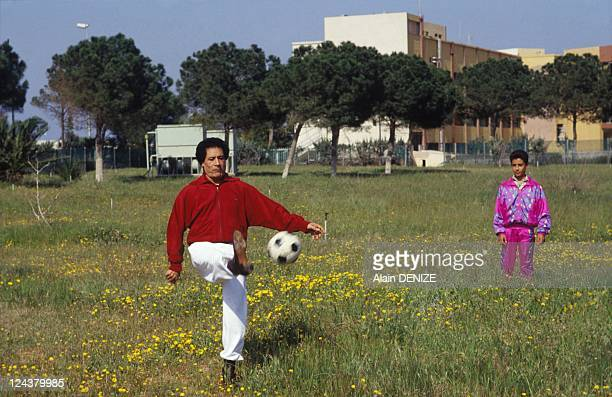 Libyan leader Muammar Gaddafi kicks a football as one his sons looks on in the military barracks of Bab alAzizia on March 18 1992 in Tripoli Libya