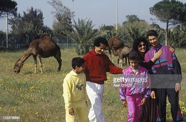 Libyan leader Muammar Gaddafi walks with wife Safia and sons Seif alArab known as Aruba Khamis and MoatassemBillah in the military barrackwith wife...