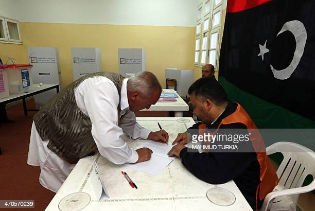 A Libyan man casts his vote to elect a constituent assembly at a polling station in the capital Tripoli on February 20 2014 Libyans went to the polls...