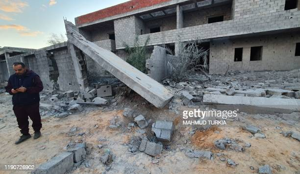 A Libyan man checks his phone on the site of a reported airstrike in the capital Tripoli's suburb of Tajoura on December 29 2019