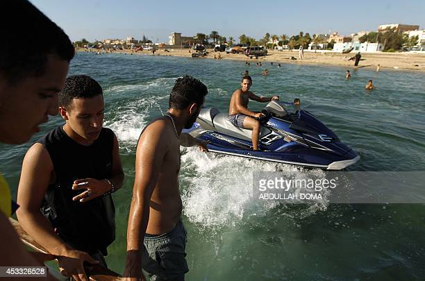A Libyan man drives a jet ski off the beach in the eastern coastal city of Benghazi on August 7 2014 The ongoing unrest in the strifetorn North...