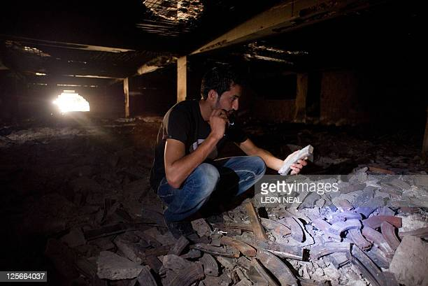 A Libyan man inspects a large pile of ammunition magazines in a former government weapons store in central Tripoli on September 19 2011 During the...