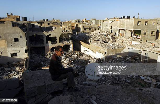 A Libyan man looks at destroyed building on March 4 2016 in Laithi district a central area that was recently reseized by forces loyal to Libya's...