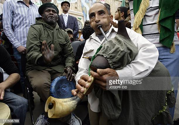 A Libyan man loyalist to Col Moamer Kadhafi plays a local bagpipe as another man drums along to patriotic songs during a rally in Tripoli's Green...