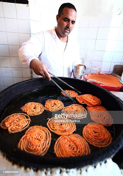 A Libyan man prepares popular traditional sweets on the first day of the Muslim fasting month of Ramadan in Tripoli on July 20 2012 Muslims fasting...