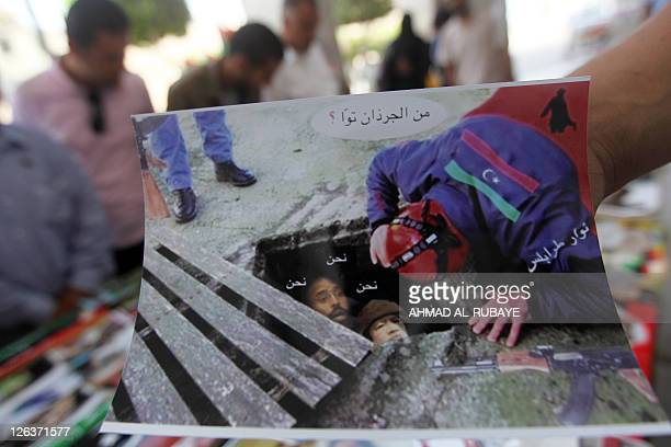 A Libyan man shows a poster depicting Libya's deposed leader Moamer Kadhafi and his son Seif alIslam as rats coming out of sewage at a kiosk selling...