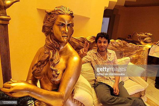 Libyan man sit on the large gilded sofa in the entrance of Aisha Gaddafi's luxury villa on August 27 2011 in Tripoli Libya Houses belonging to the...