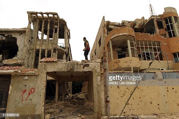 Libyan man stands atop a destroyed building on February 29 2016 as he works to get it reconnected to electricity in a central area that was recently...