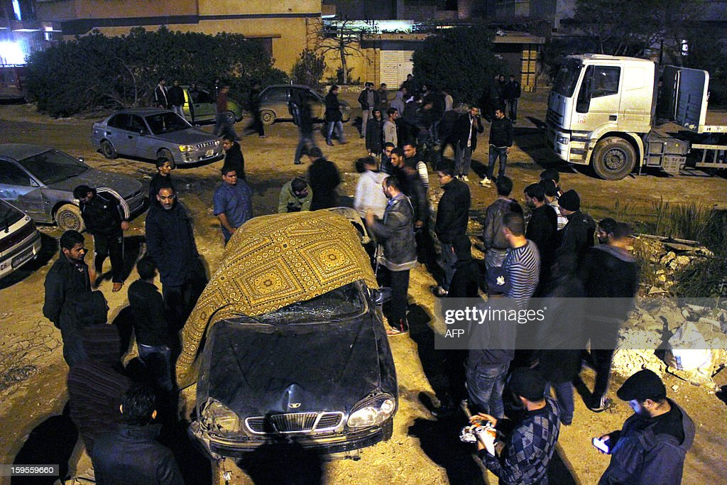 Libyan men gather around a damaged car at the site of an explosion which killed police Sergeant Salah Miftah Wizry late on January 15, 2013 in the eastern Libyan city of Benghazi. The number of attacks targeting military and police officers, including ones who served the former regime, has increased in past weeks despite efforts by the new authorities to boost security in the Mediterranean city.