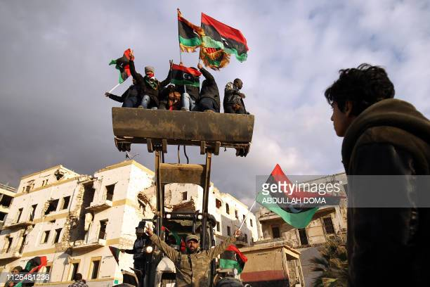 TOPSHOT Libyan men on a bulldozer wave the national flag as they gather to mark the eighth anniversary of the uprising in Libya's second city of...