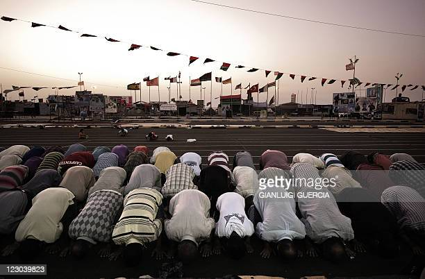 Libyan men perform the evening prayer at the end of the first fasting day of Islam's holy month of Ramadan in the rebel stronghold of Benghazi on...