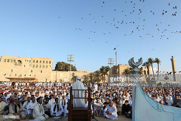 Libyan men pray as they mark the start of Eid alFitr at the Martyrs' Square in Tripoli on August 19 2012 Muslims around the world celebrate Eid...