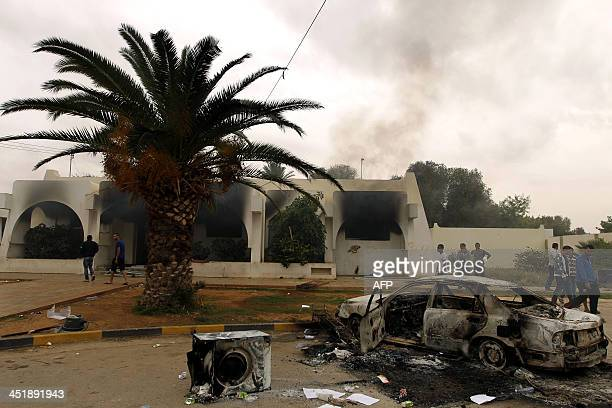 Libyan men stand outside a building used by Ansar alSharia militia after it was torched by residents on November 25 2013 in Benghazi Military...