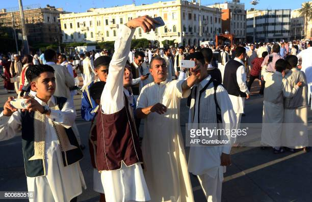 Libyan men take photos as Muslim worshippers gather at the Martyrs' Square in the capital Tripoli to perform Eid alFitr prayers on June 25 2017 to...