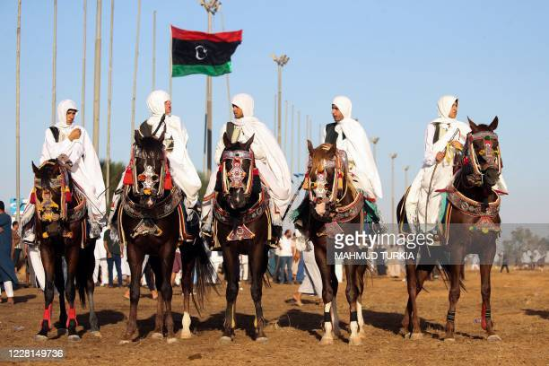 Libyan men, wearing traditional costumes, ride horses during a popular equestrian festival near the capital Tripoli on August 21, 2020.