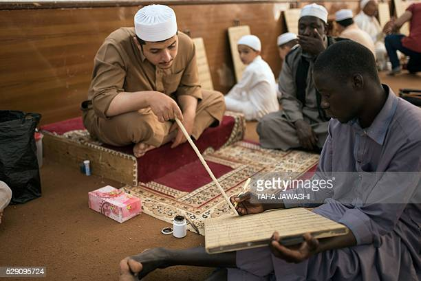 Libyan men write on their prayer boards verses from the Quran Muslim's holy book at alAsmarya Quranic school on May 4 2016 in Libya's coastal city of...