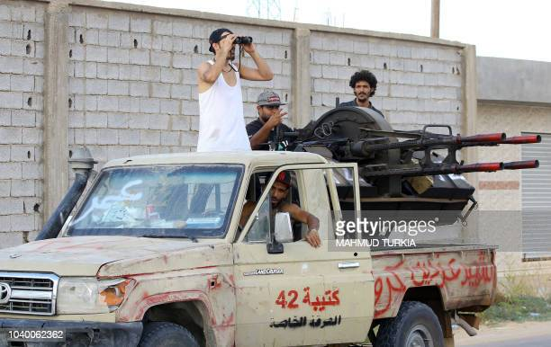 Libyan militiamen loyal to the Government of National Accord Libya's internationally recognised government keep watch from a position south of the...