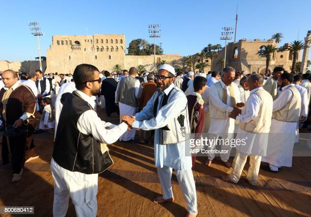 Libyan Muslim worshippers greet each other as they gather at the Martyrs' Square in the capital Tripoli to perform Eid alFitr prayers on June 25 2017...
