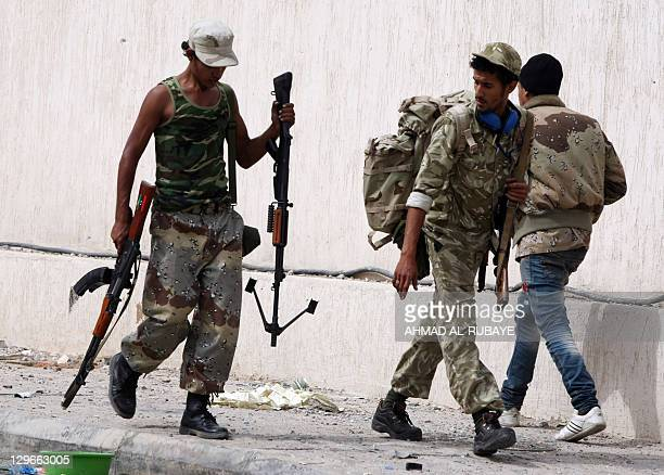 A Libyan National Transitional Council fighter carries a weapon in his left hand used by a captured loyalist diehard on October 19 2011 during a...