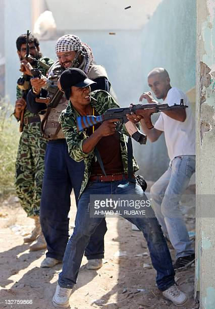 A Libyan National Transitional Council fighter fires at loyalist troops as street battles continue to take control of Sirte on October 14 2011 Forces...