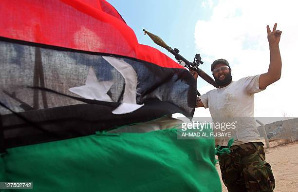A Libyan National Transitional Council fighter flashes the victory sign in the outskirts of Sirte on September 28 2011 AntiKadhafi forces urged NATO...