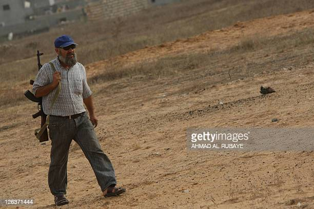 A Libyan National Transitional Council fighter is pictured as NTC officials show journalists on September 25 2011 what they they claim was a mass...