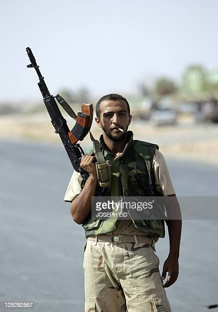 A Libyan National Transitional Council fighter poses for a picture with his machinegun in the desert city of Bani Walid southeast of Tripoli on...
