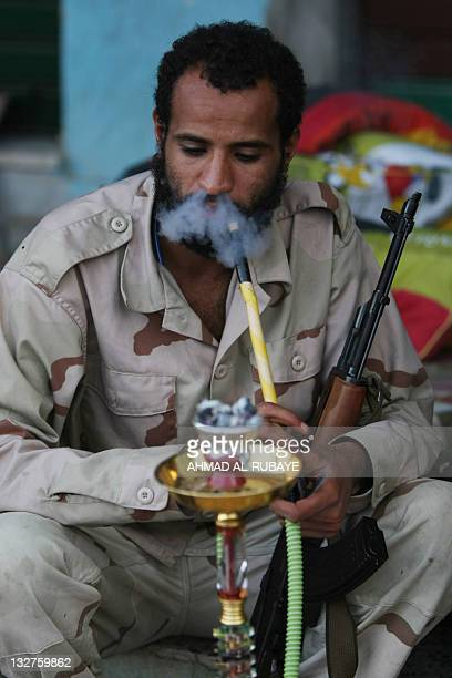 A Libyan National Transitional Council fighter smokes a waterpipe the city center of the Libyan port of Sirte on October 13 as Libya's new regime...