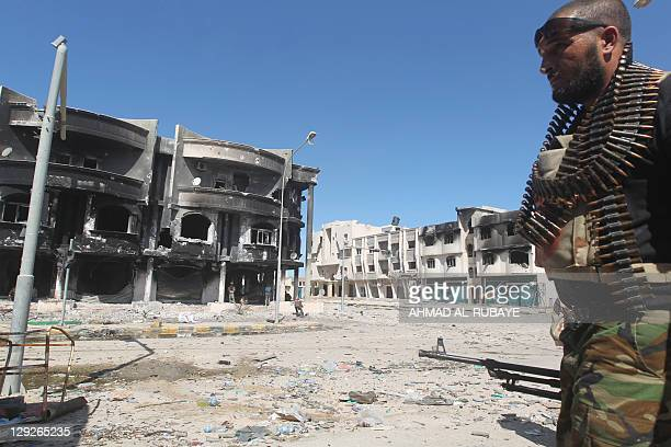 A Libyan National Transitional Council fighter walks with his gun during fighting against proMoamer Kadhafi gunmen in central Sirte on October 15 as...