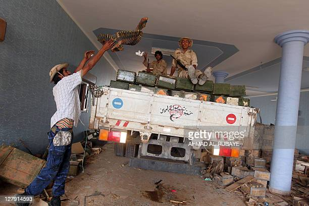 Libyan National Transitional Council fighters a truck with weapons after finding a cache inside a house in the village of Qasr Abu Hadi the...