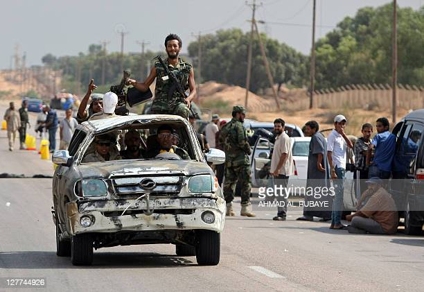 Libyan National Transitional Council fighters drive a damaged car past people fleeing Sirte on the eastern outskirts of the city on October 1 2011...