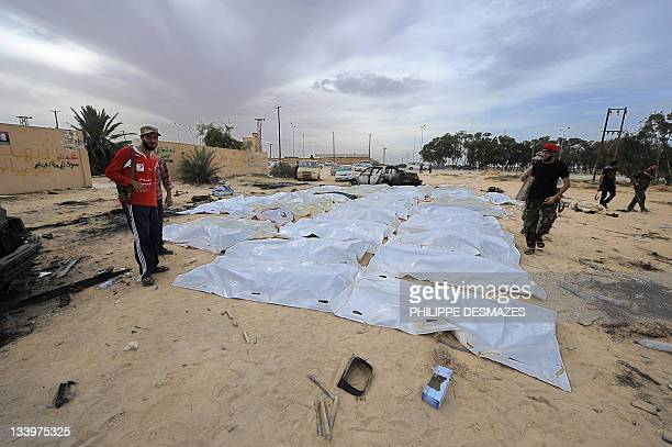 Libyan National Transitional Council fighters gather around body bags carrying the remains of loyalist troops believed to have been killed in a NATO...
