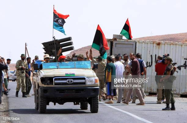 Libyan National Transitional Council fighters gather on the northern outskirts of Bani Walid on September 30 as forces from Libya's new regime...