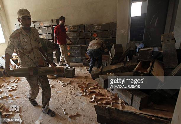Libyan National Transitional Council fighters inspect ammunition found at a weapons' cache belonging to loyalist troops in the outskirts of Sirte on...