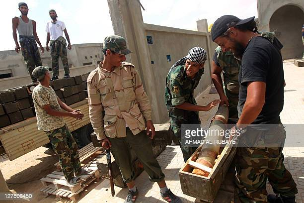 Libyan National Transitional Council fighters inspect ammunition boxes found in a weapons' cache belonging to loyalist troops in the outskirts of...