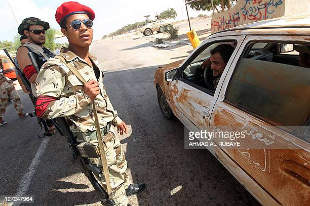 Libyan National Transitional Council fighters man a checkpoint near the frontline in the eastern suburbs of Sirte on September 27 2011 NTC fighters...