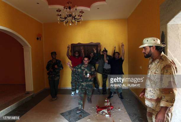 Libyan National Transitional Council fighters pose for a picture inside a house of a Kadhafi loyalist in the village of Qasr Abu Hadi the birthplace...