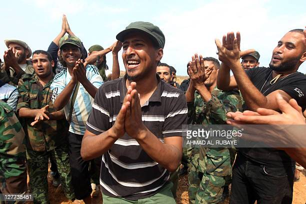 Libyan National Transitional Council fighters rejoice after firing dozens of shells towards Sirte from the city's eastern edge to target what they...