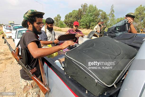 Libyan National Transitional Council fighters search the belongings of people fleeing Sirte on the eastern outskirts of the city on October 1 2011...